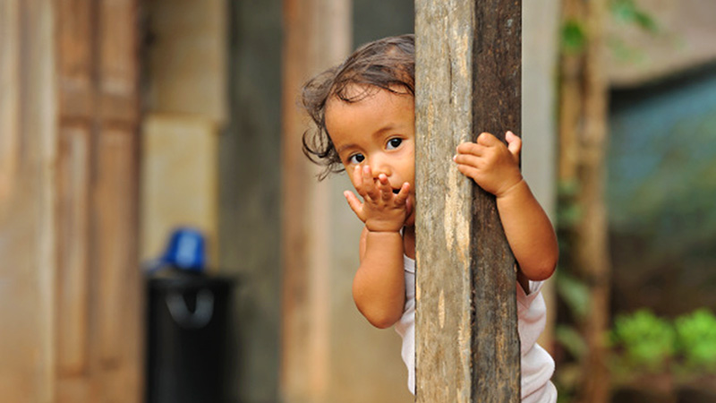 Child hiding behind a wooden post outside.